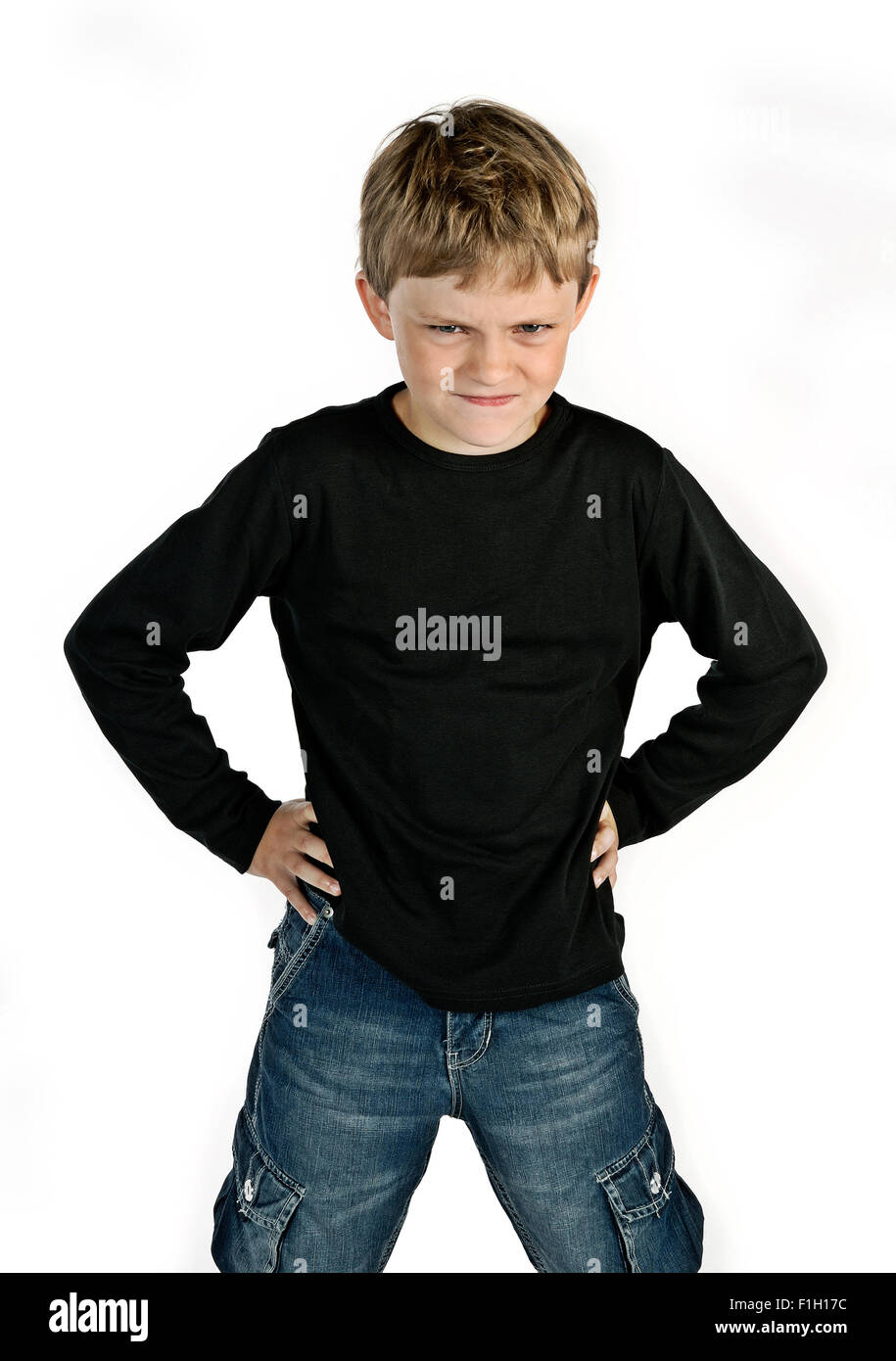 Angry little boy braces his hands on his hips. - Stock Image