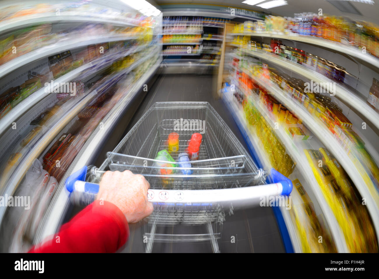 customer pushing shopping trolley at speed in supermarket - Stock Image