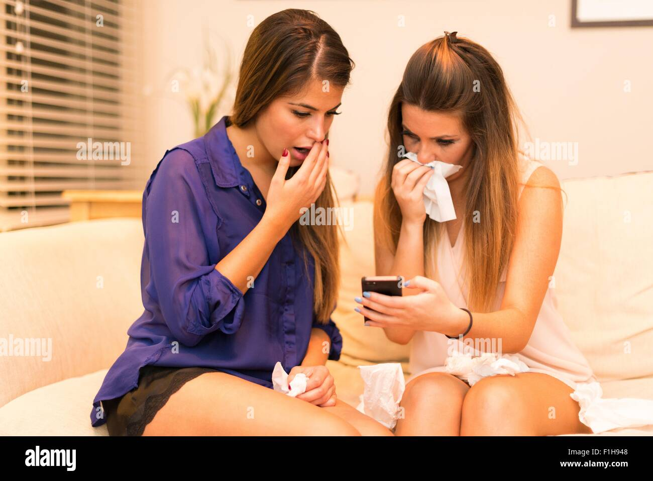 Two young women, sitting on sofa looking at smartphone, shocked expression - Stock Image
