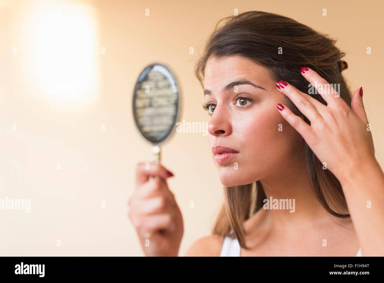Young woman looking in hand mirror - Stock Image