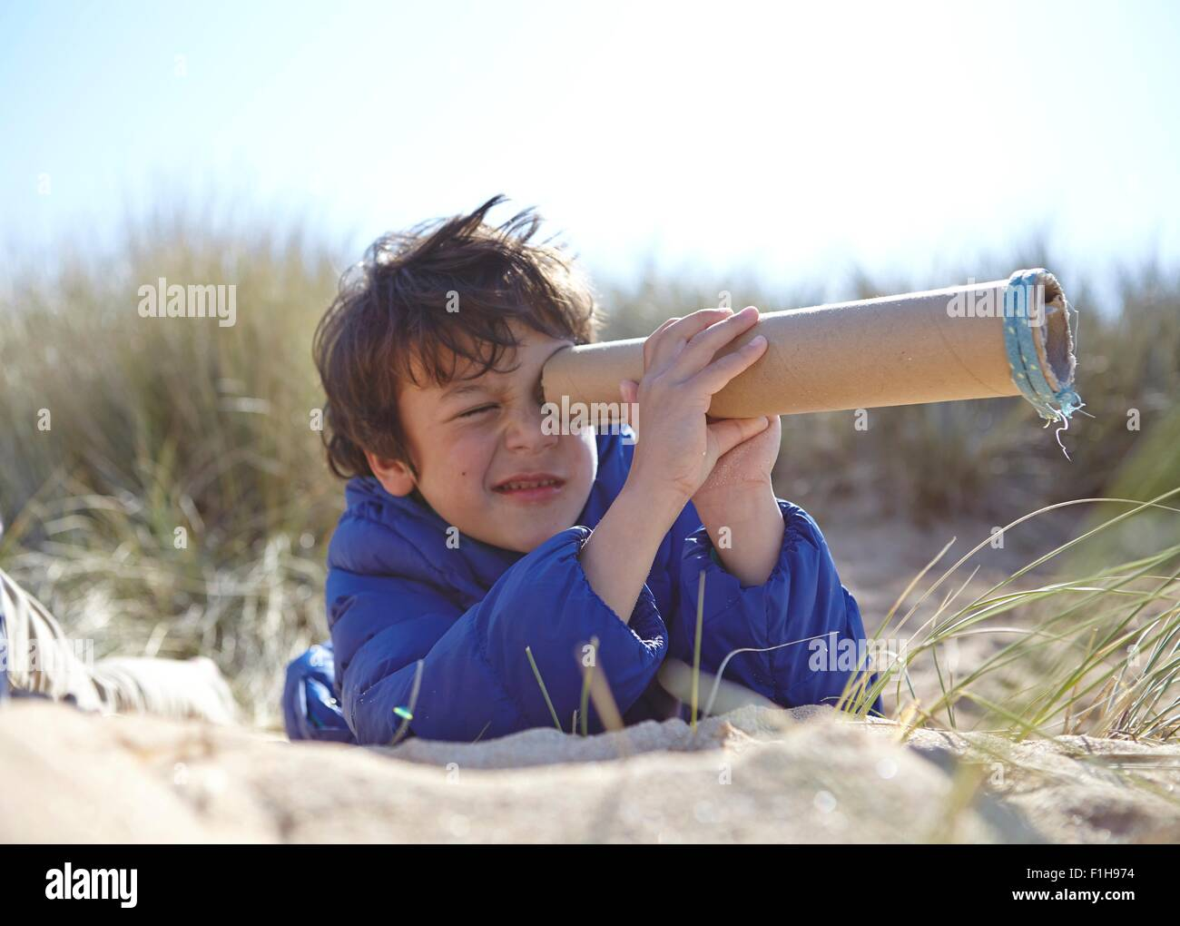 Young boy on beach, looking through pretend telescope - Stock Image