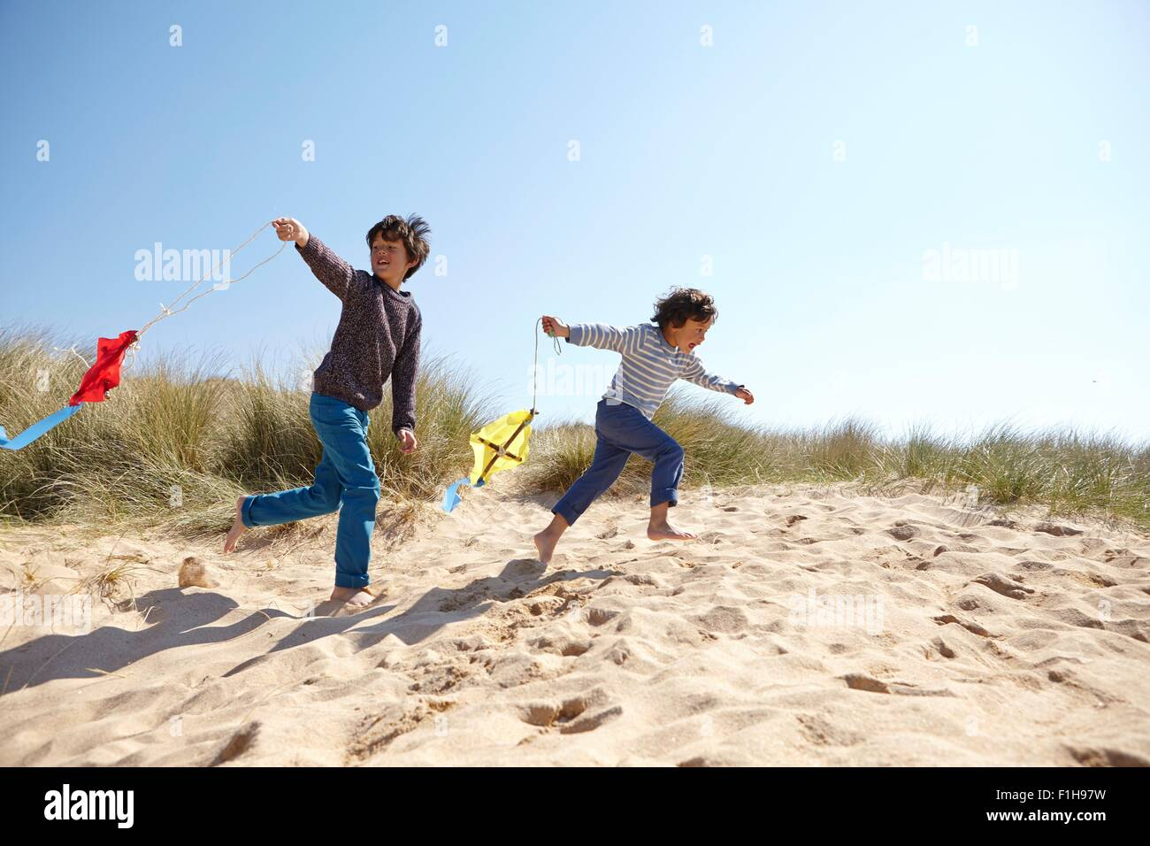 Two young boys, flying kites on beach - Stock Image