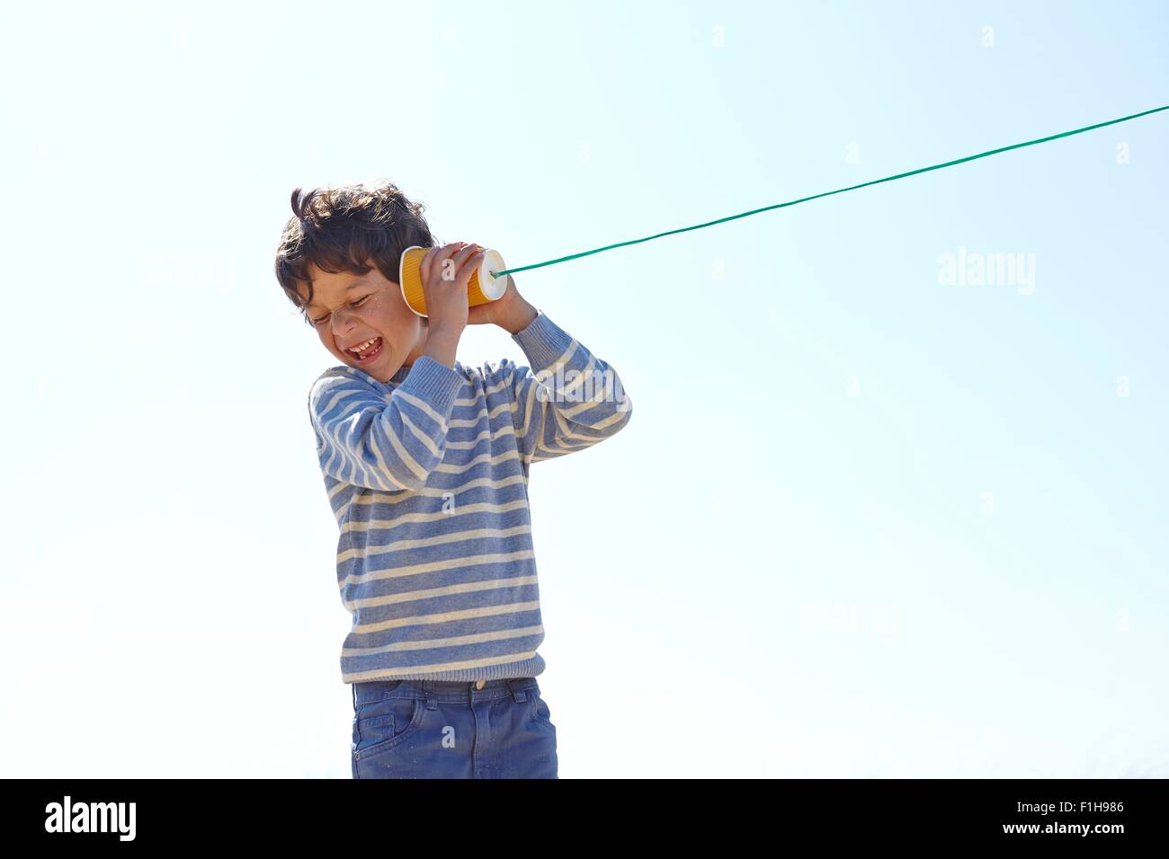 Young boy, holding cup and string telephone to ear - Stock Image