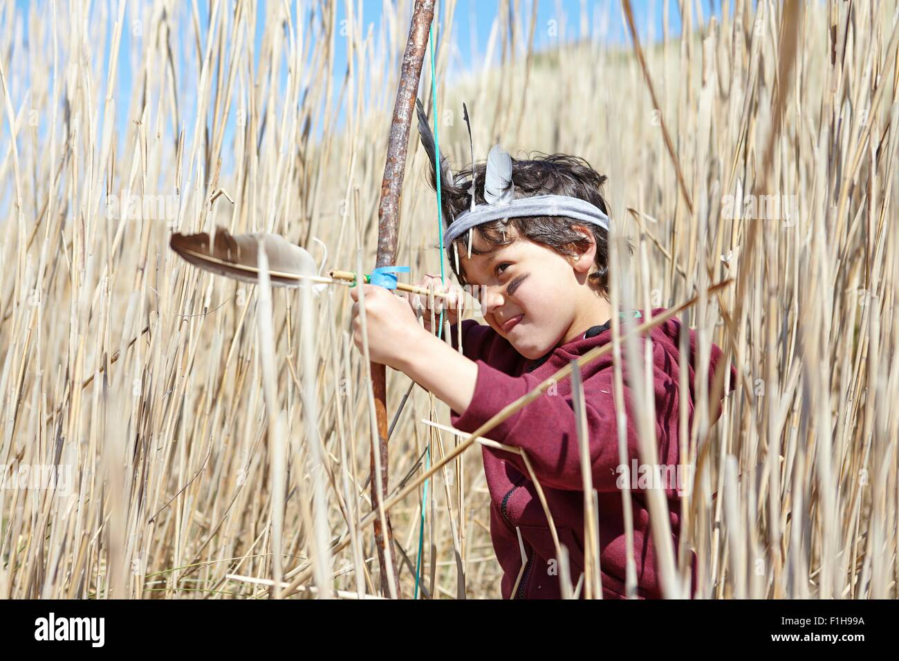 Young boy wearing fancy dress, holding home-made bow and arrow - Stock Image