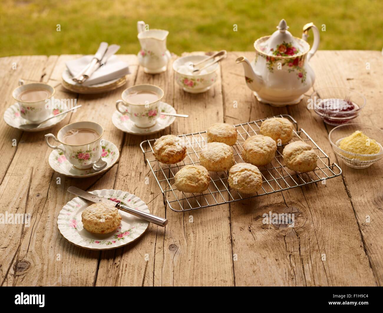 Table with afternoon tea of with fresh baked scones with jam and clotted cream - Stock Image