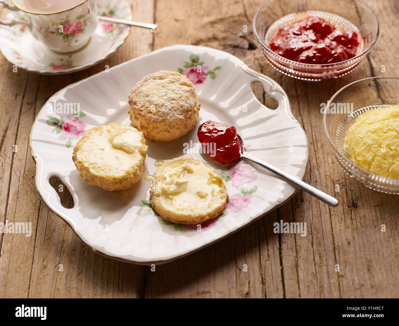 Afternoon tea of with fresh baked scones with jam and clotted cream - Stock Image