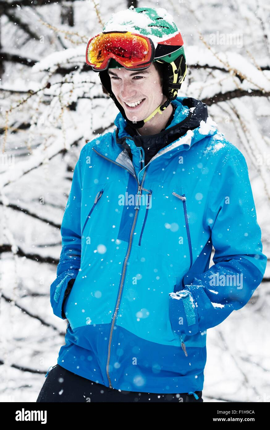 Young man wearing skiwear in snow, portrait - Stock Image