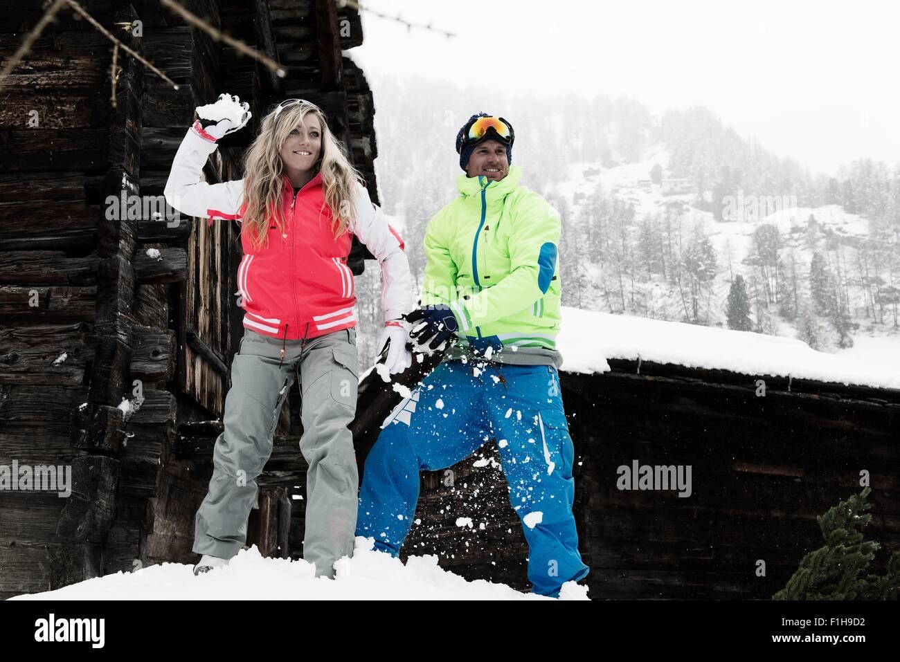 Man and woman throwing snowballs - Stock Image