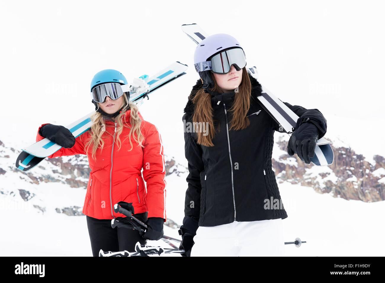 87ea032f373 Women wearing helmets and ski goggles holding skis