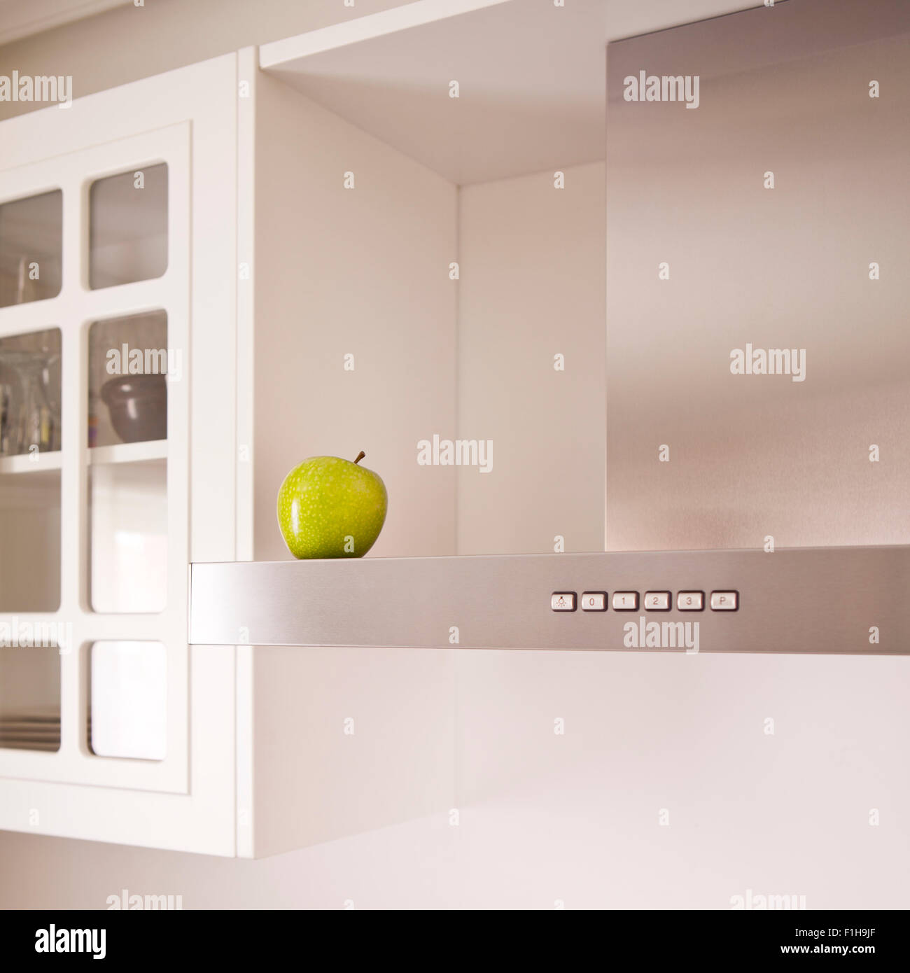 Green apple symbolizing cleanness in a modern white kitchen. Stock Photo