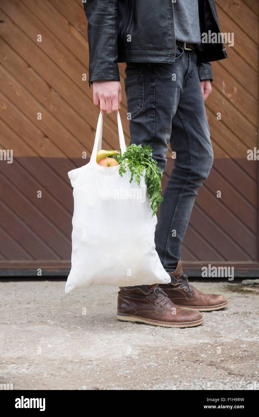 Teenage boy carrying reusable shopping bags full of fresh fruit and veg - Stock Image