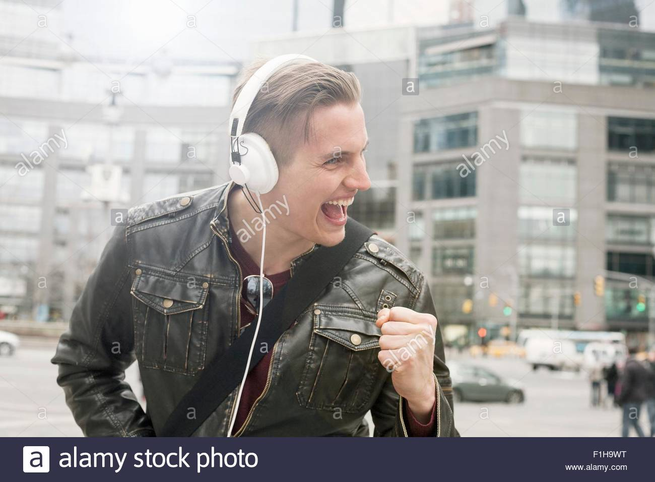 Young man on street listening to headphones with clenched fist,  New York, USA - Stock Image