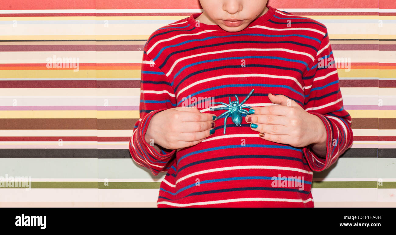 Little girl holding a plastic toy spider in her hands. Conceptual image of childhood curiosity, fantasy and adventure. - Stock Image