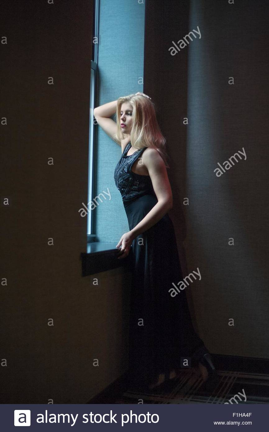 Beautiful young woman with hand in hair looking through hotel window - Stock Image