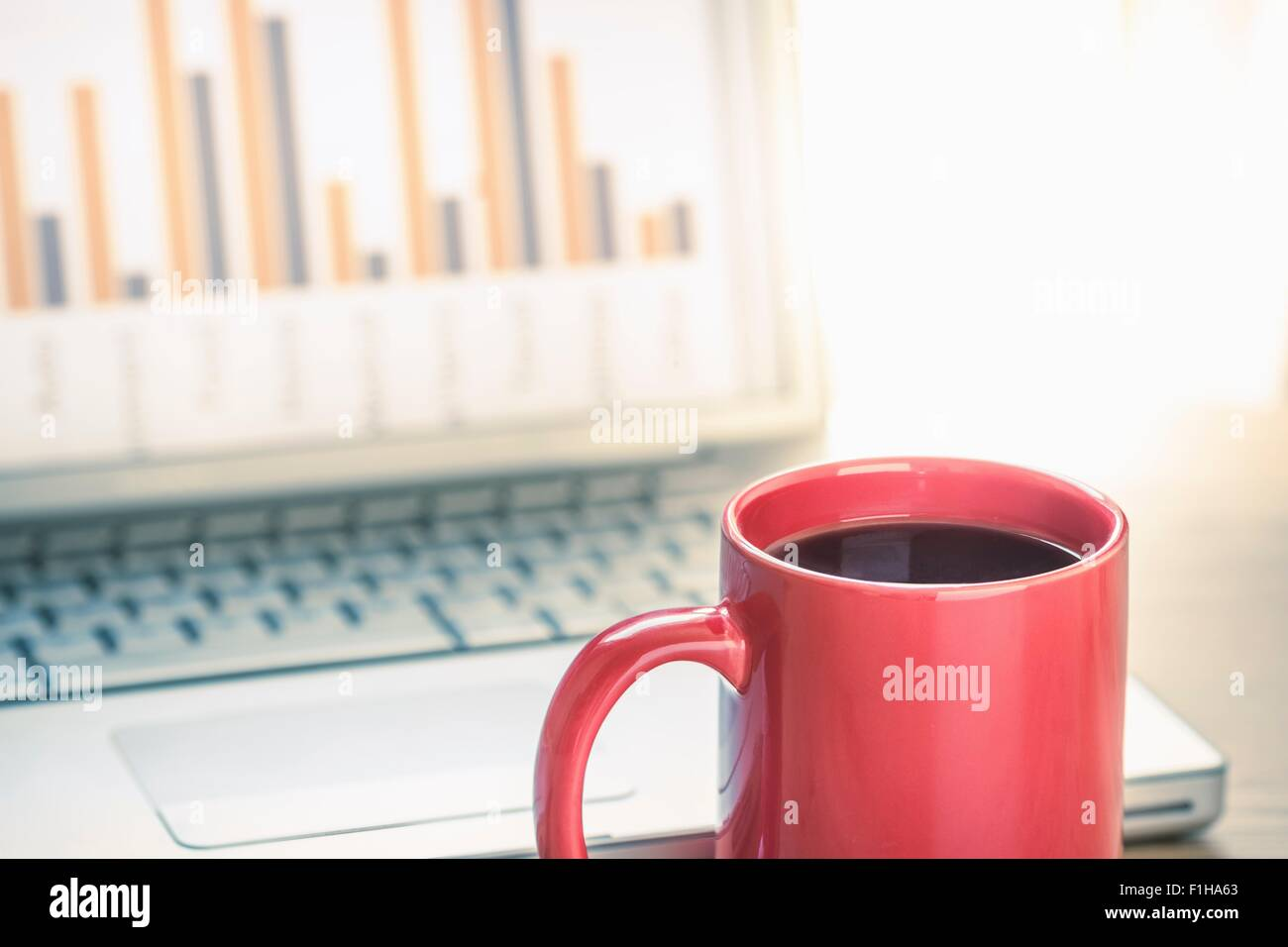 Close up still life of black coffee and bar finance chart on laptop screen - Stock Image