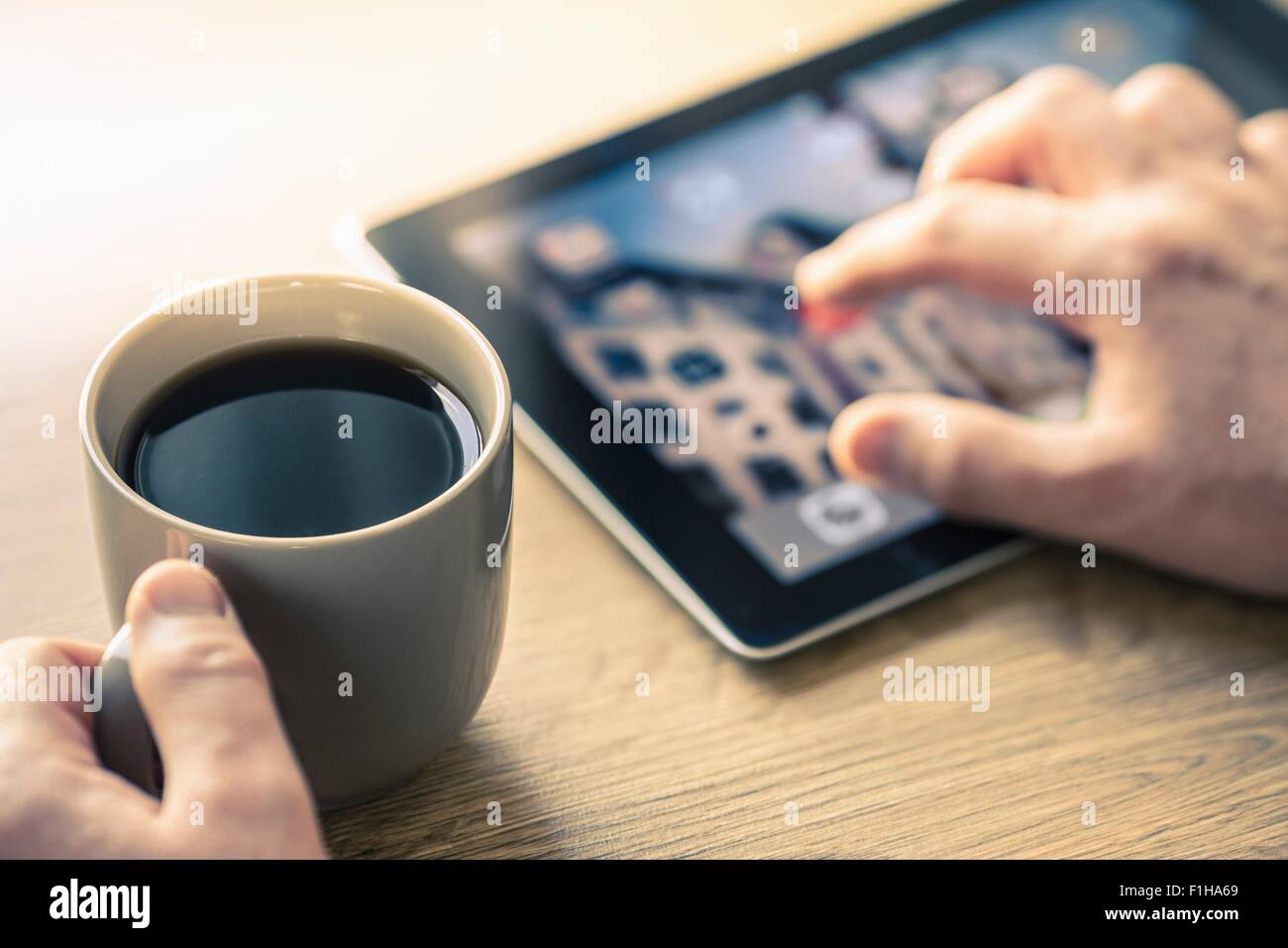 Hands of man using digital tablet touchscreen - Stock Image