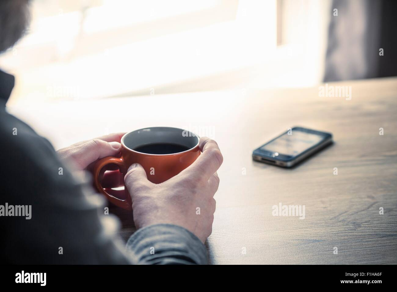 Over shoulder view of man drinking coffee with smartphone on desk - Stock Image