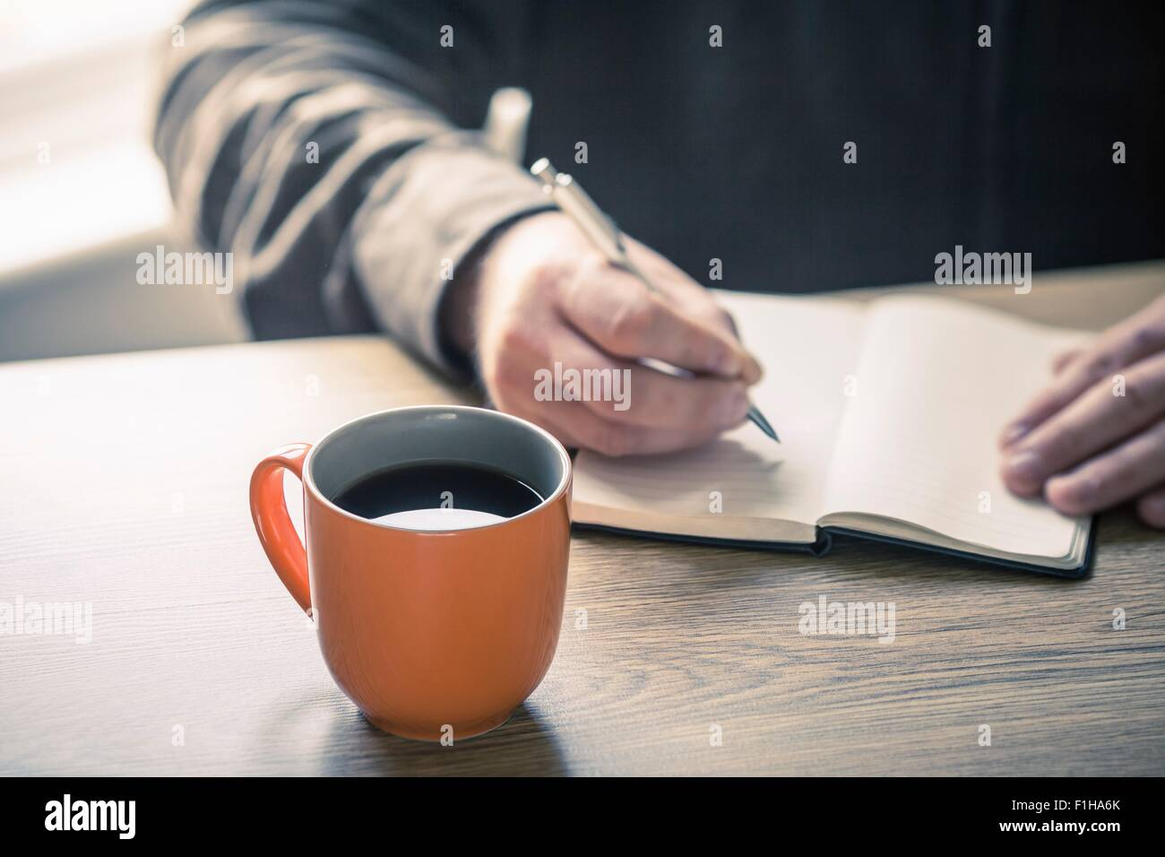 Hands of mature man writing in notebook - Stock Image