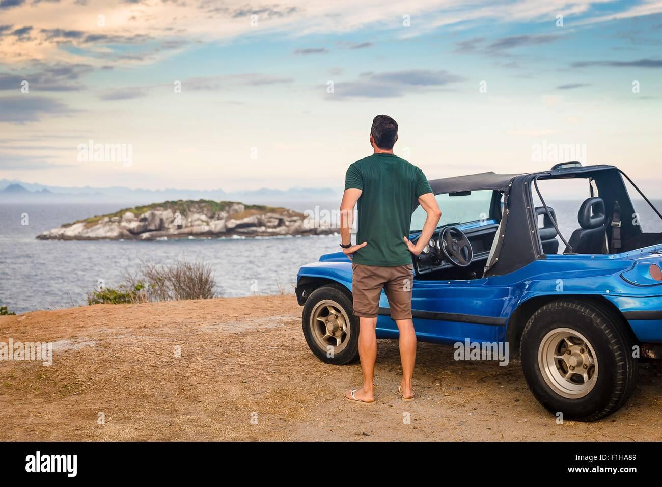 Rear view of male tourist looking out to Branca island, Buzios, Rio de Janeiro, Brazil - Stock Image