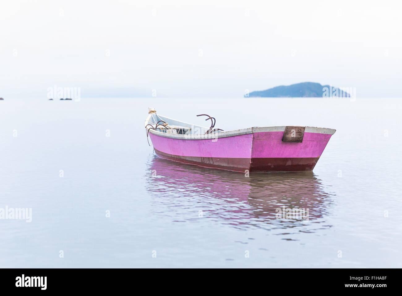 Anchored pink rowing boat, Manguinhos, Buzios, Rio de Janeiro, Brazil - Stock Image