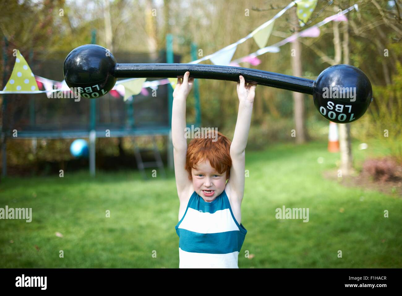 Young boy lifting pretend barbell, outdoors - Stock Image