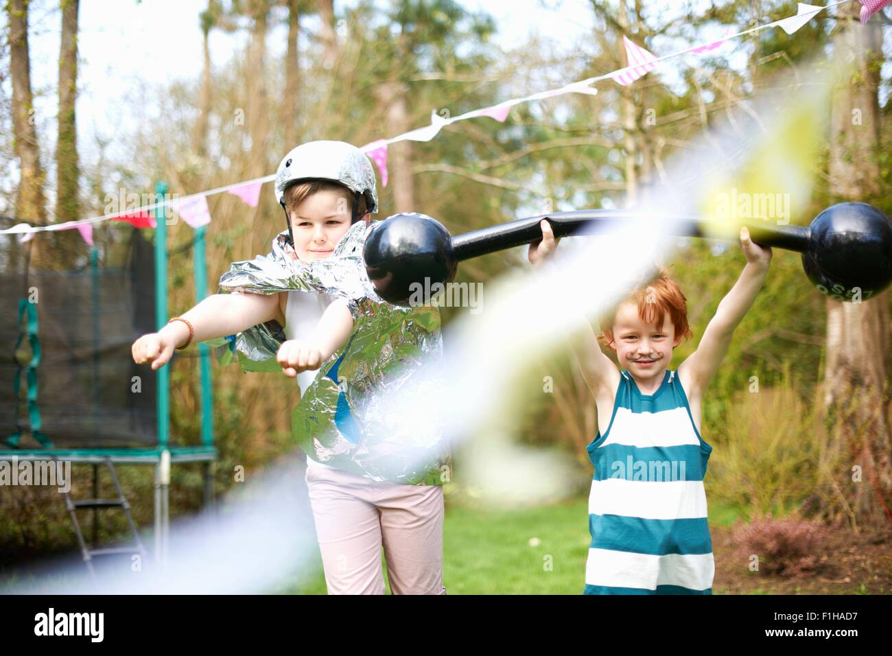 Young children wearing fancy dress, playing in garden - Stock Image