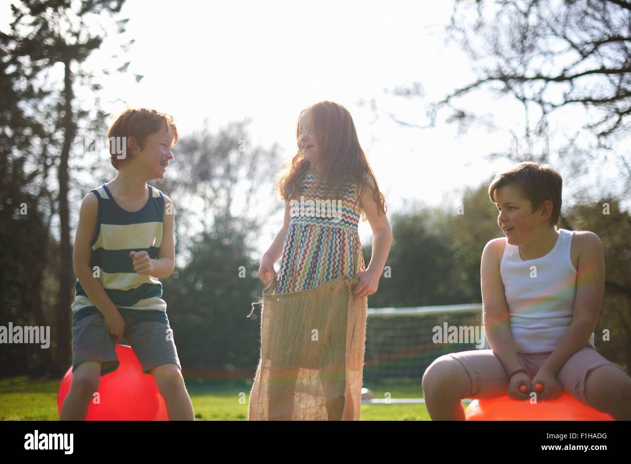 Young children on inflatable hopper and standing in sack, ready for race Stock Photo