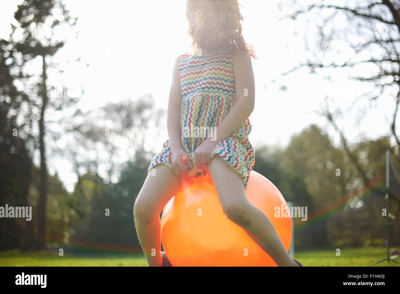 Young girl bouncing on inflatable hopper - Stock Image