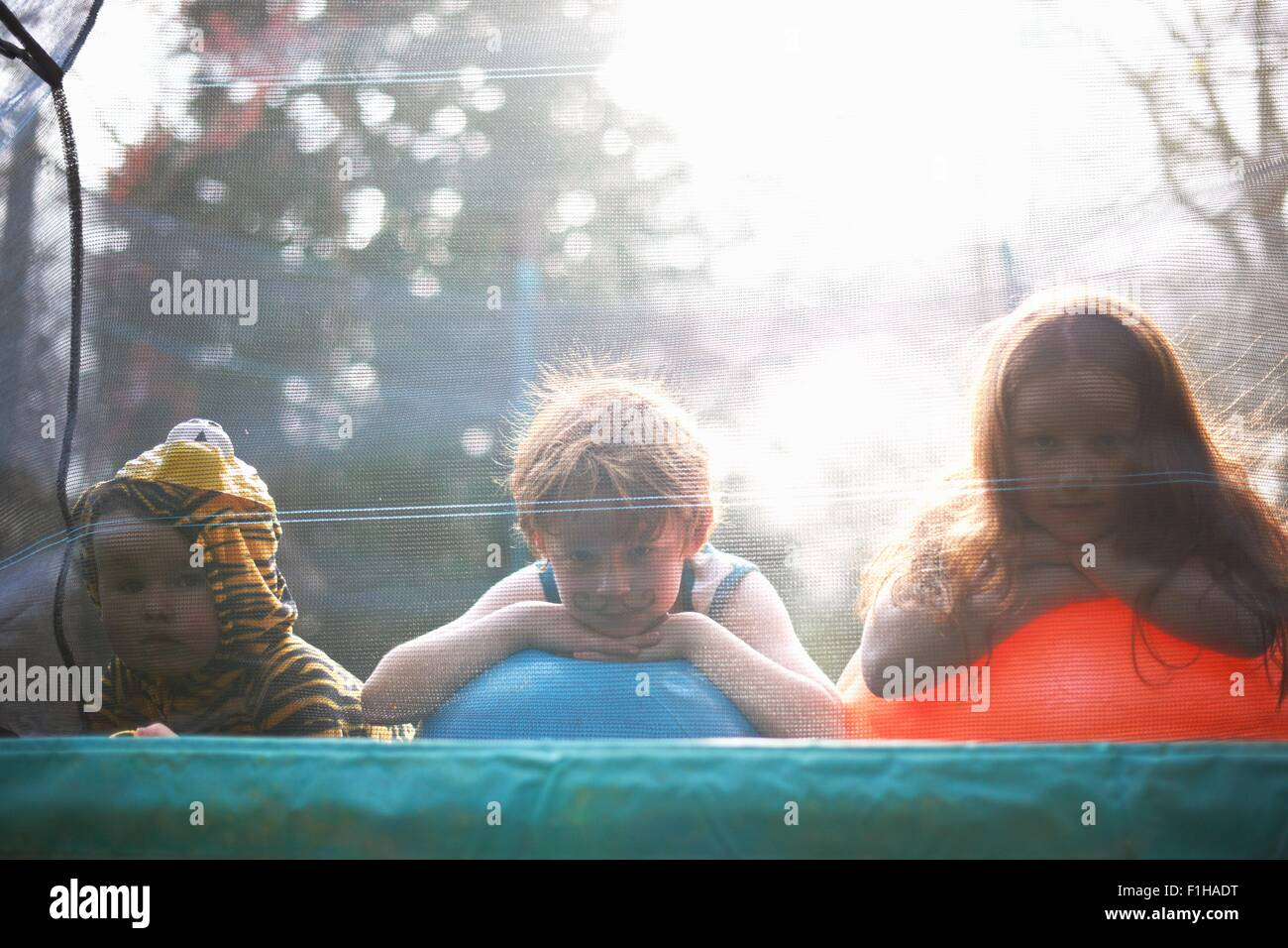 Young children looking out from garden trampoline - Stock Image