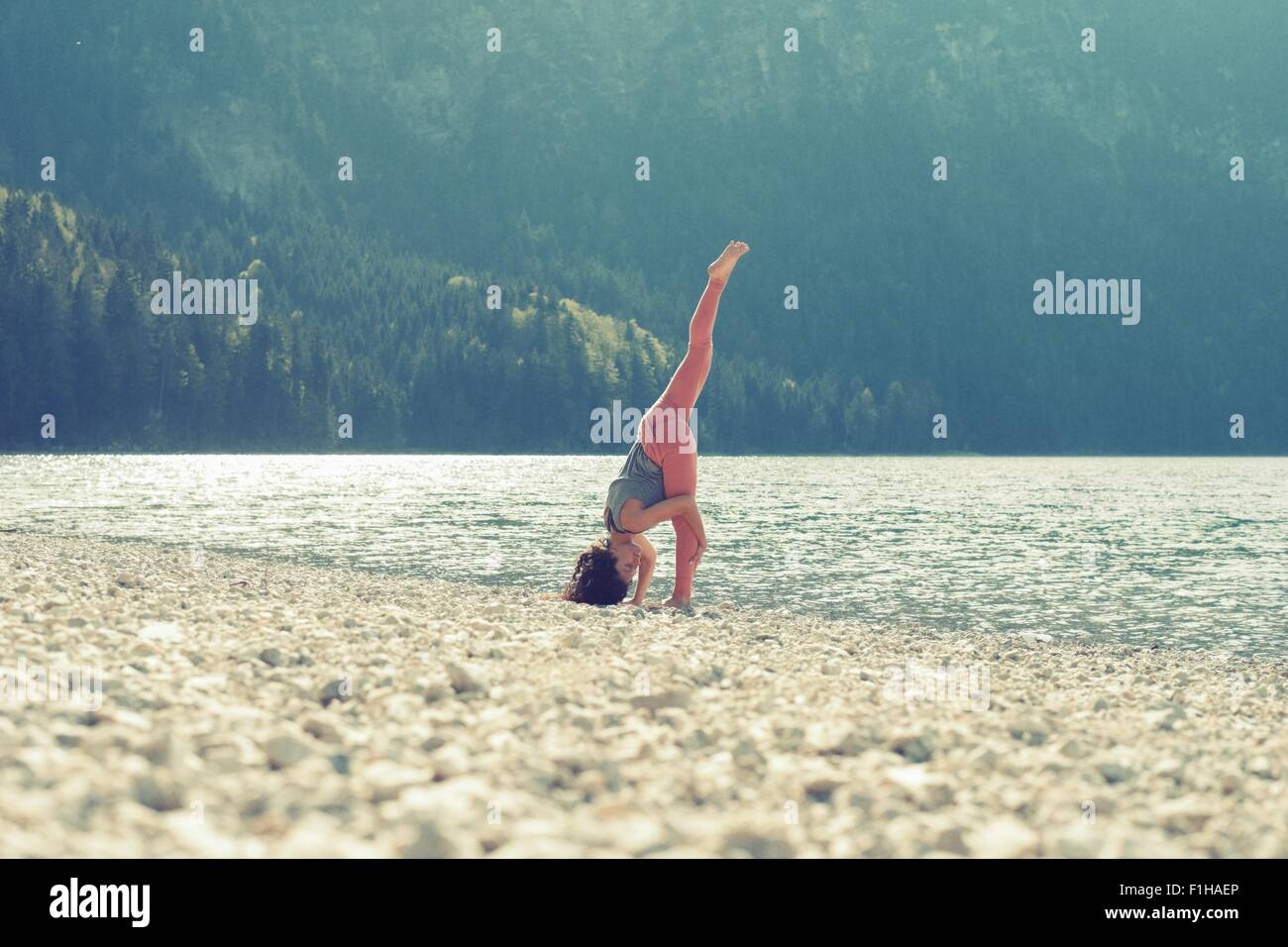Mid adult woman, beside lake, in yoga position Stock Photo