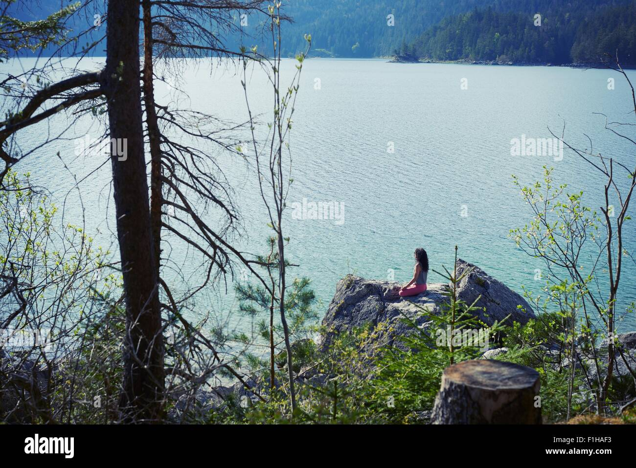 Mid adult woman, sitting on rock, in yoga position, rear view - Stock Image