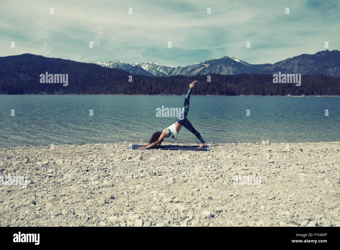 Mid adult woman, beside lake, in yoga position - Stock Image