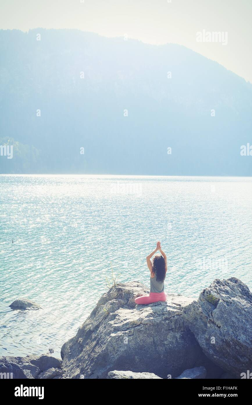 Mid adult woman, sitting on rock, beside lake, in yoga position, rear view - Stock Image