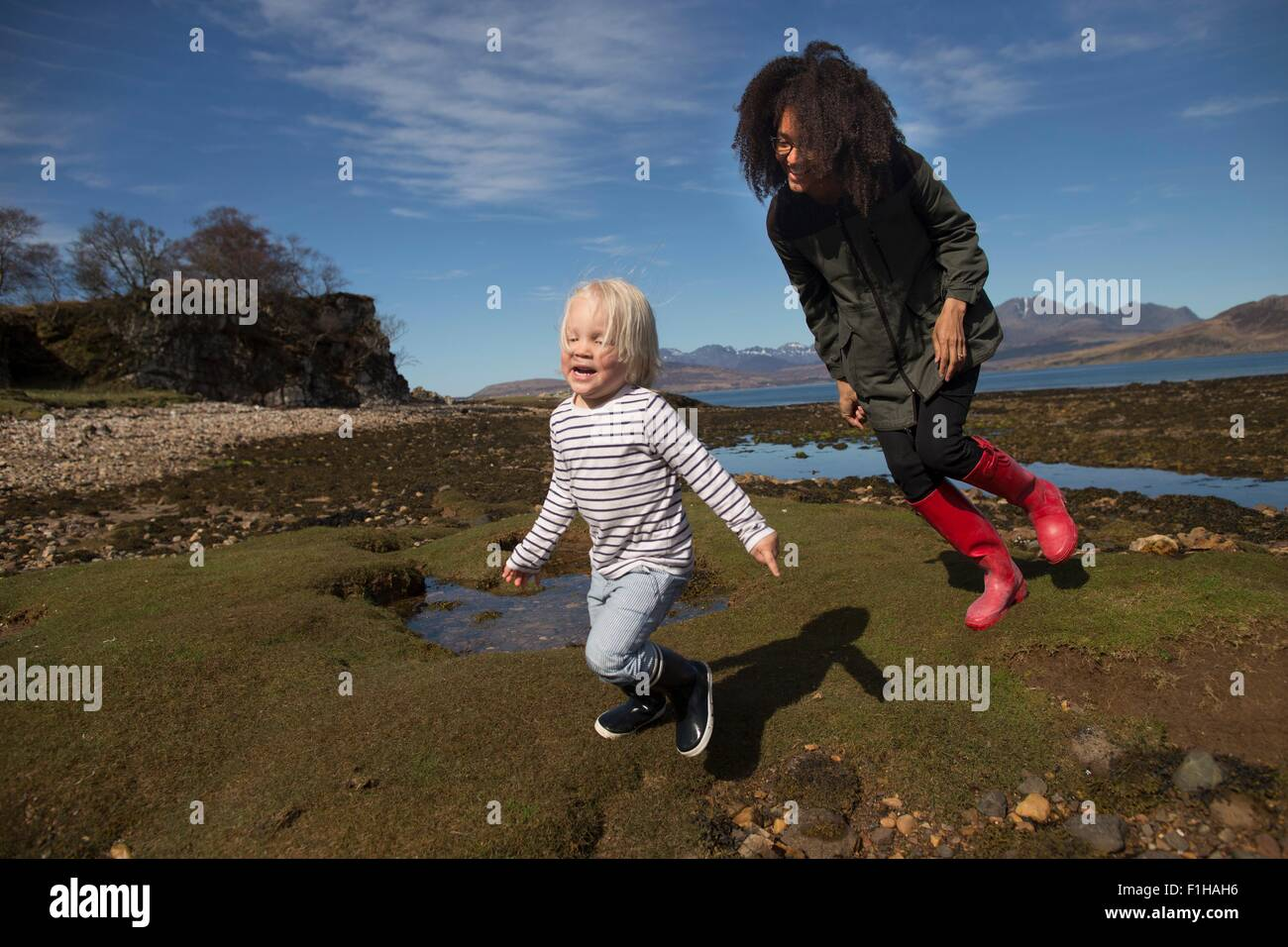 Mother and son running on grass - Stock Image