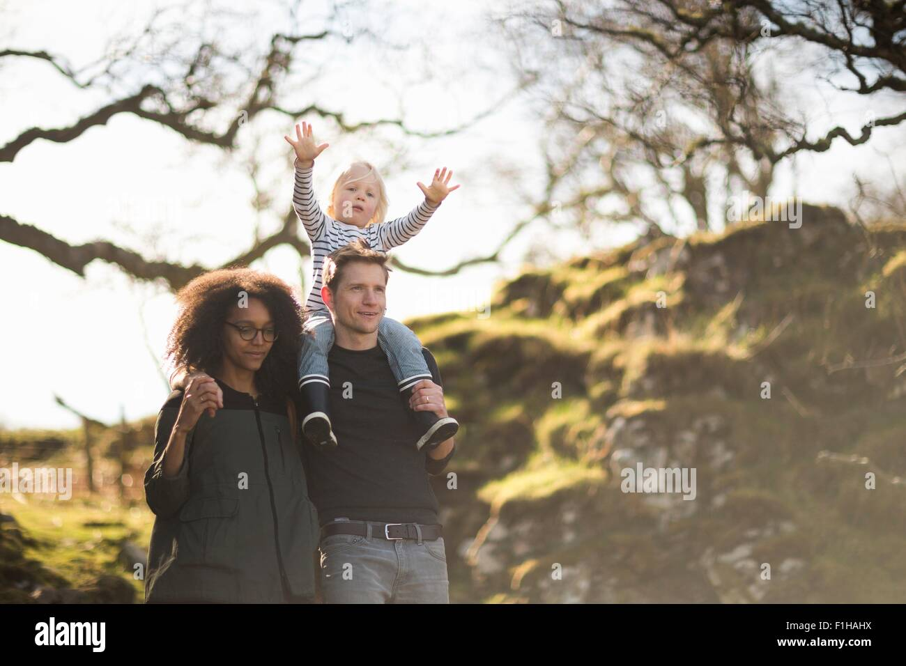 Family on walk, father carrying son on shoulders - Stock Image