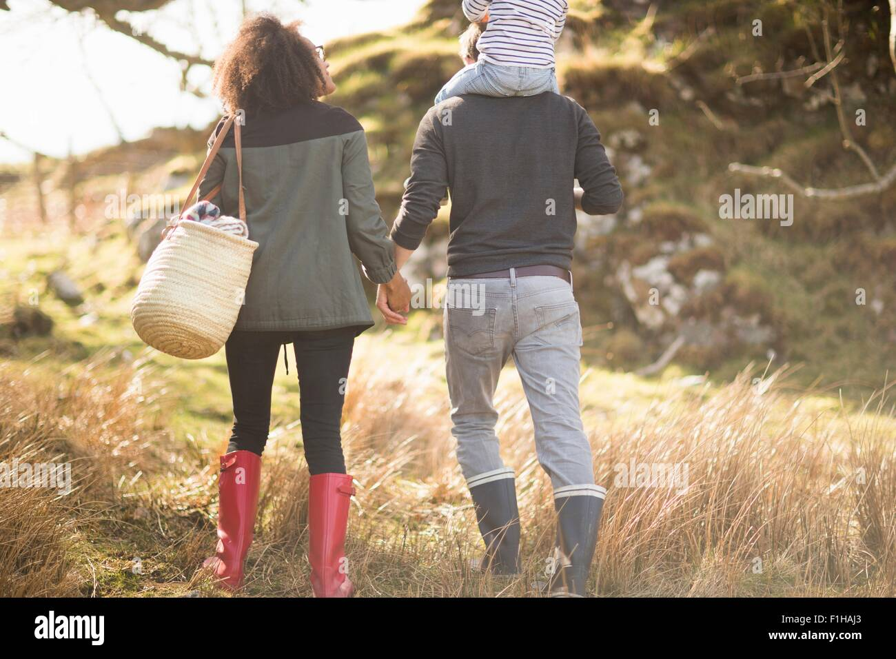 Mid adult couple on walk holding hands - Stock Image