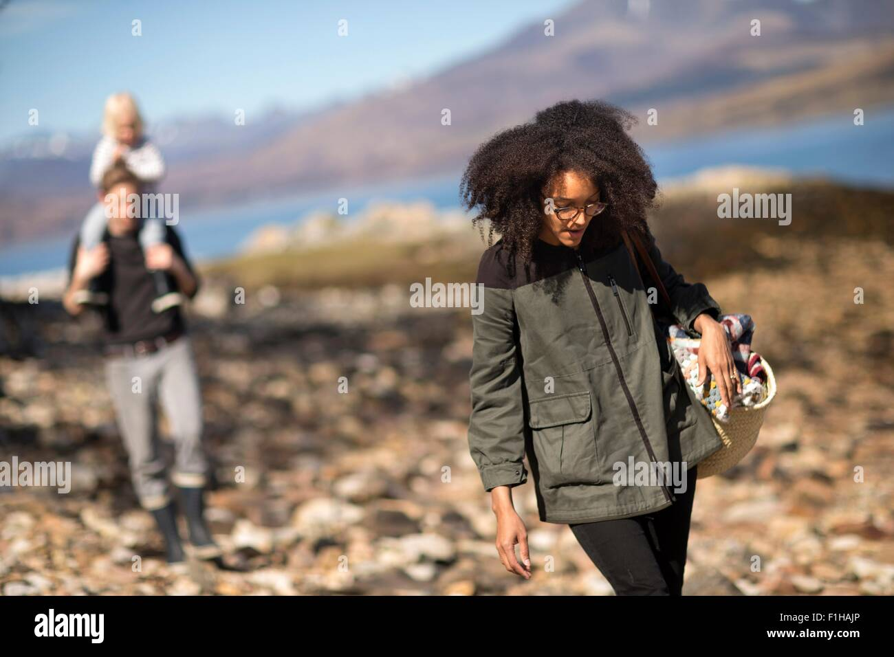 Woman walking with man and child in background - Stock Image