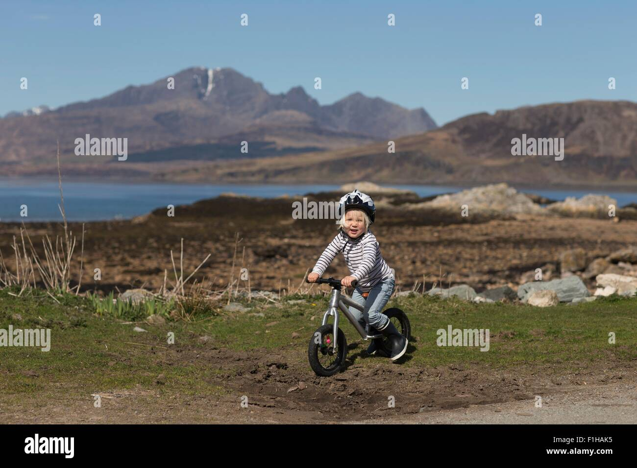 Boy riding bike, Lake Eishort, Isle of Skye, Hebrides, Scotland - Stock Image