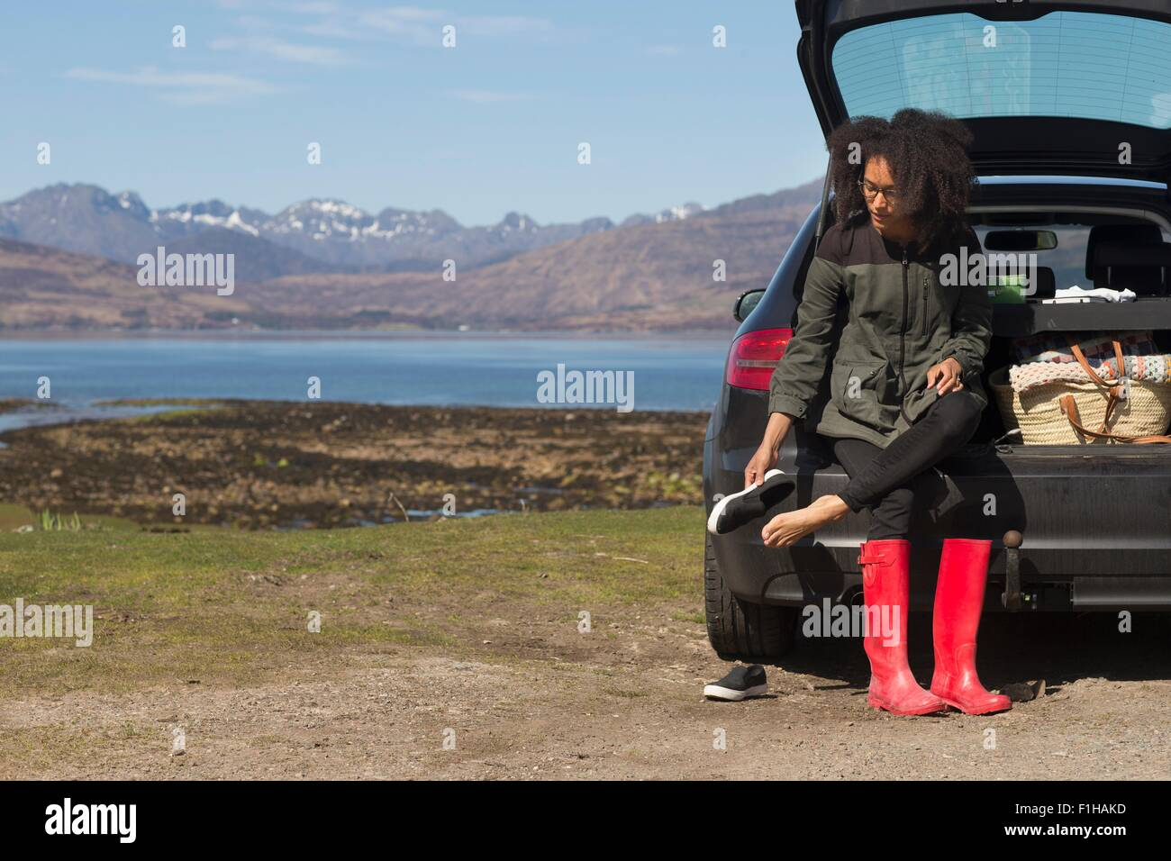Mid adult woman sitting on car boot putting shoes on, Loch Eishort, Isle of Skye, Hebrides, Scotland - Stock Image