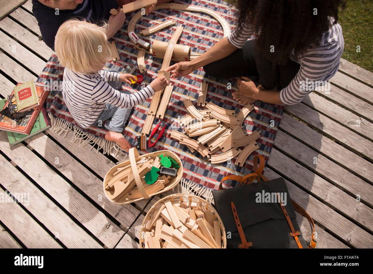 Mother and son playing with wooden toy train track, high angle Stock Photo