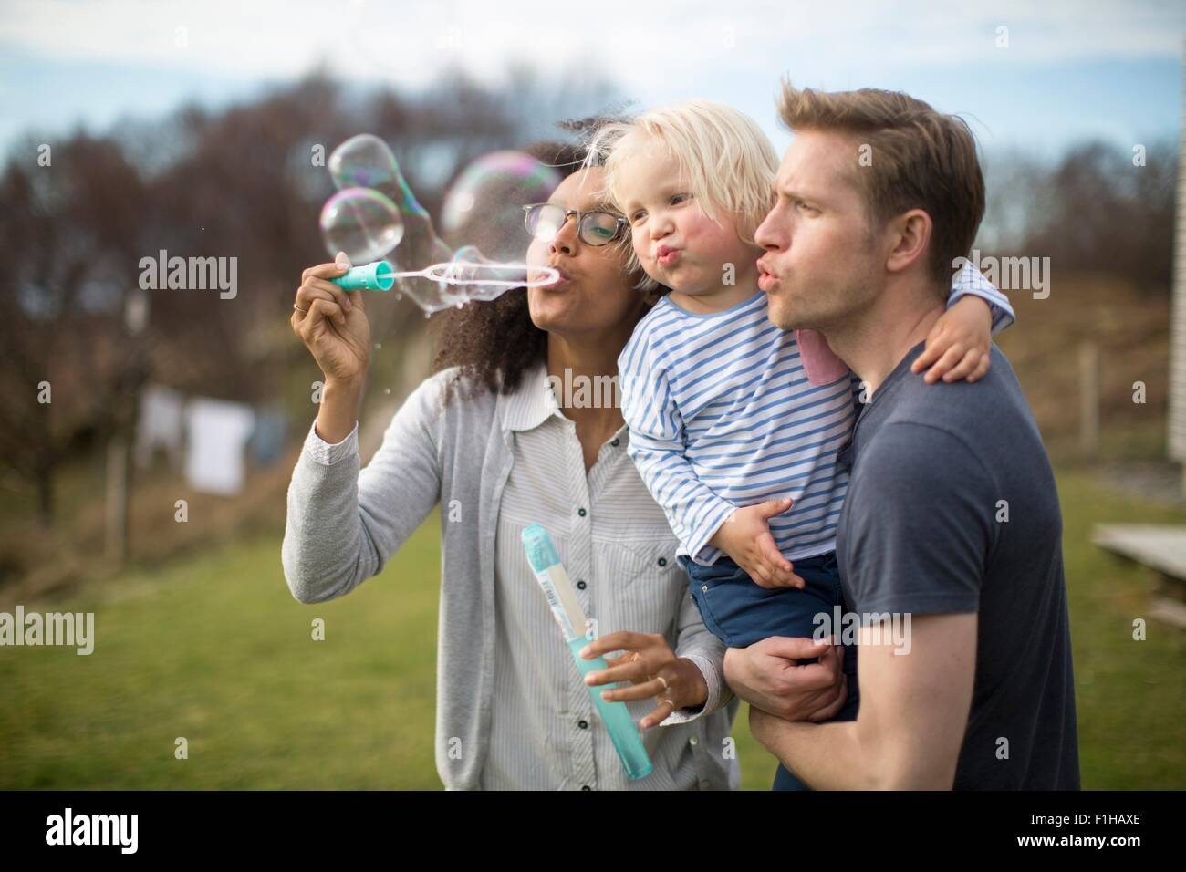 Mother blowing bubbles, father holding son - Stock Image