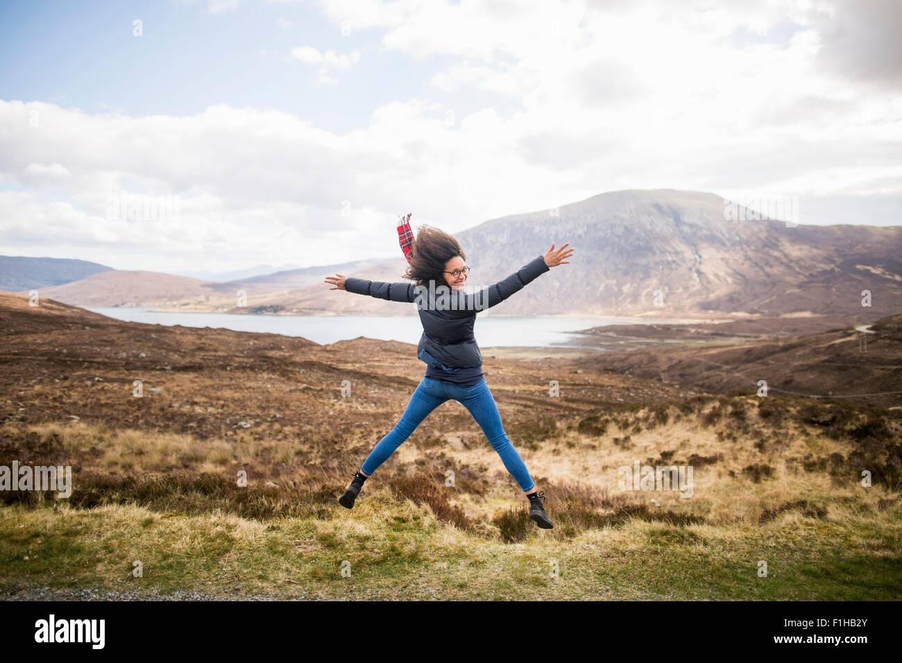 Mid adult woman in mountains doing star jump, Isle of Skye, Hebrides, Scotland Stock Photo
