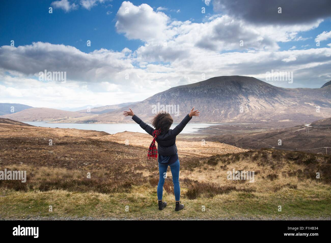 Mid adult woman in mountains with arms up, Isle of Skye, Hebrides, Scotland - Stock Image