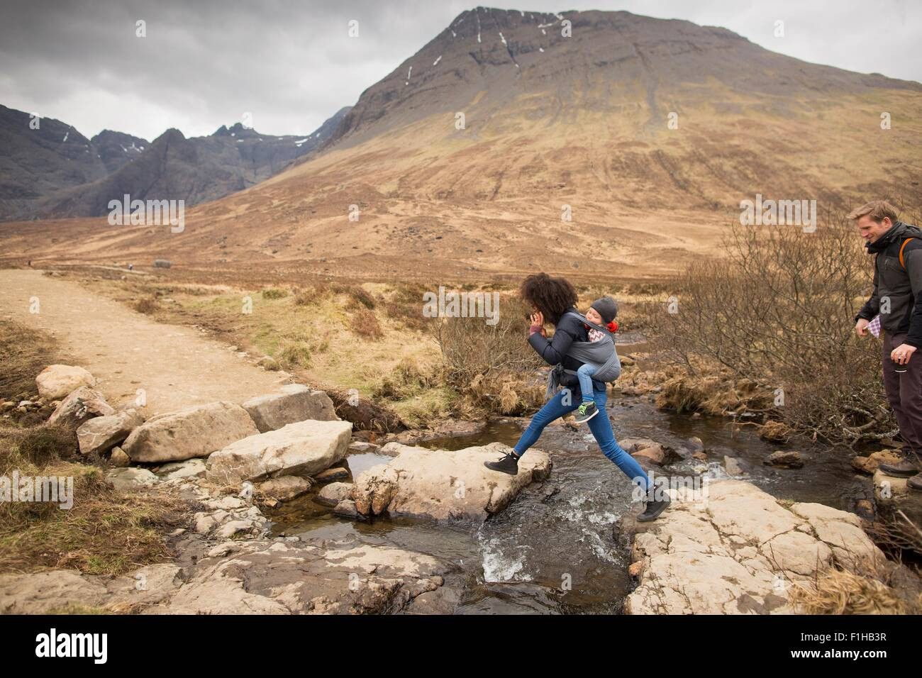 Woman leaping over stream, Fairy Pools, near Glenbrittle, Isle of Skye, Hebrides, Scotland - Stock Image