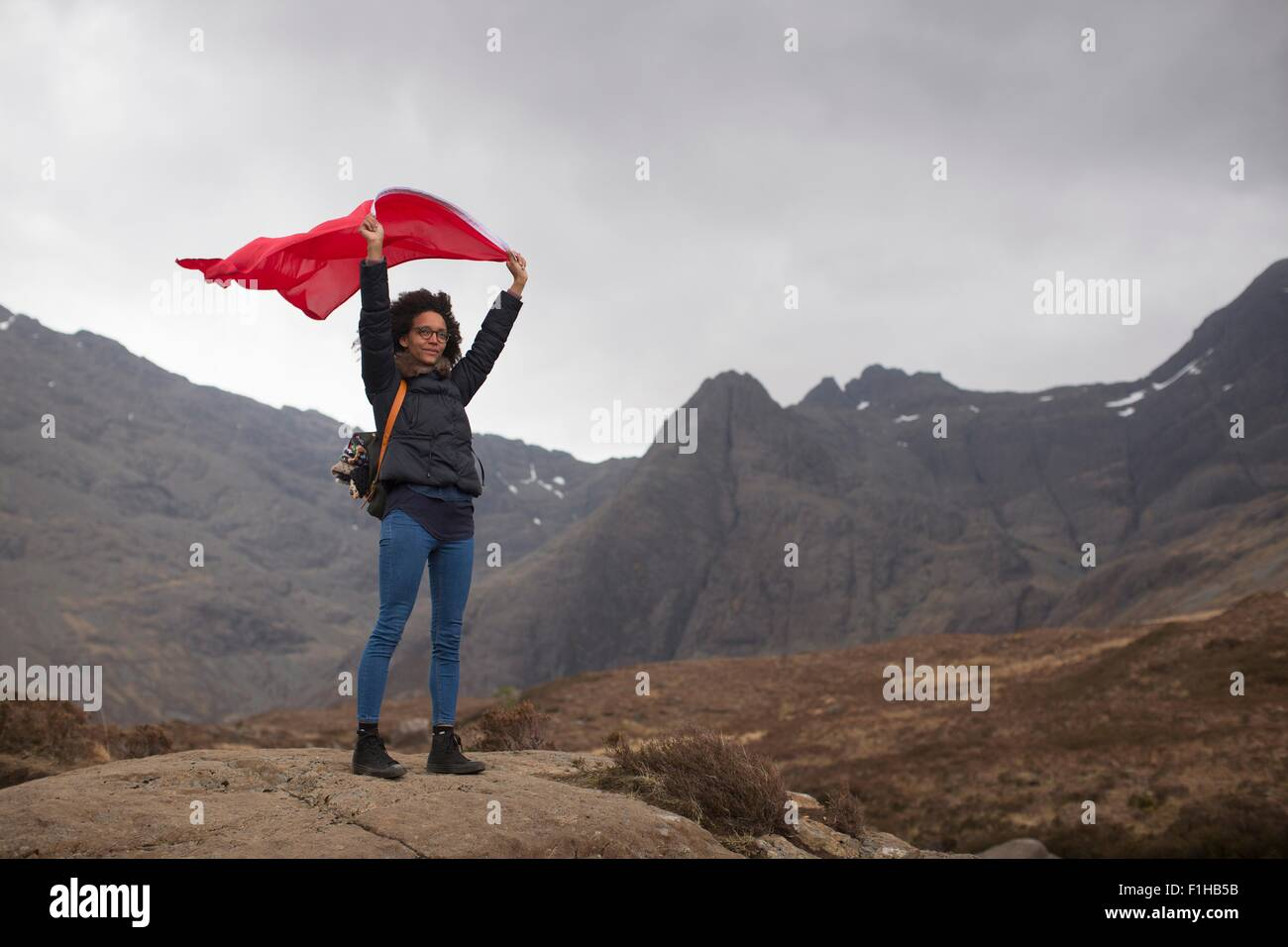 Woman holding red flag in mountains, Fairy Pools, Isle of Skye, Hebrides, Scotland - Stock Image
