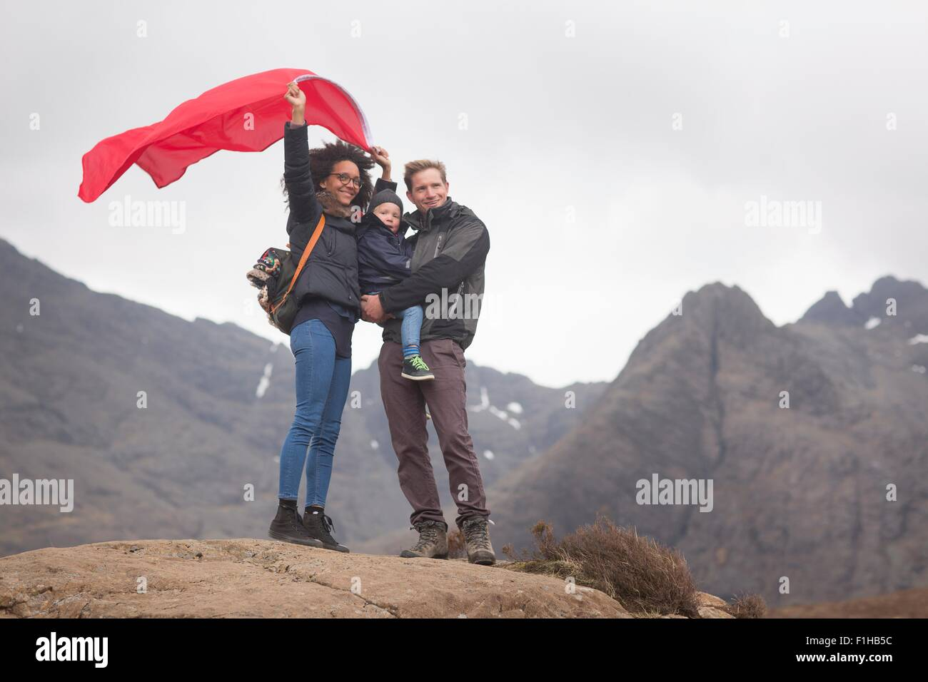 Family holding red flag in mountains, Fairy Pools, Isle of Skye, Hebrides, Scotland - Stock Image