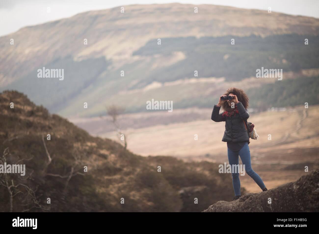 Woman using binoculars, Fairy Pools, Isle of Skye, Hebrides, Scotland - Stock Image