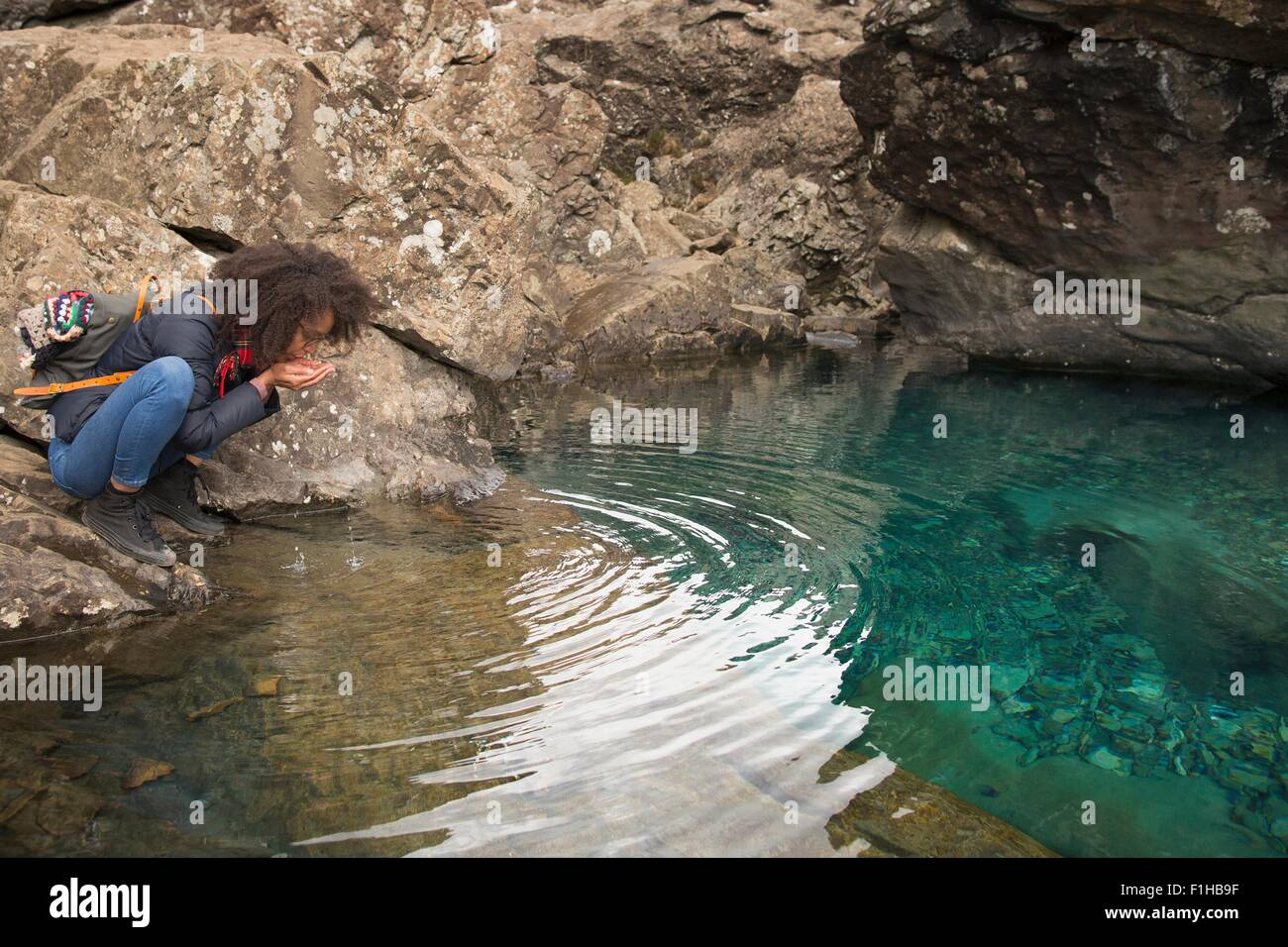 Woman drinking water from cupped hands, Fairy Pools, Isle of Skye, Hebrides, Scotland - Stock Image