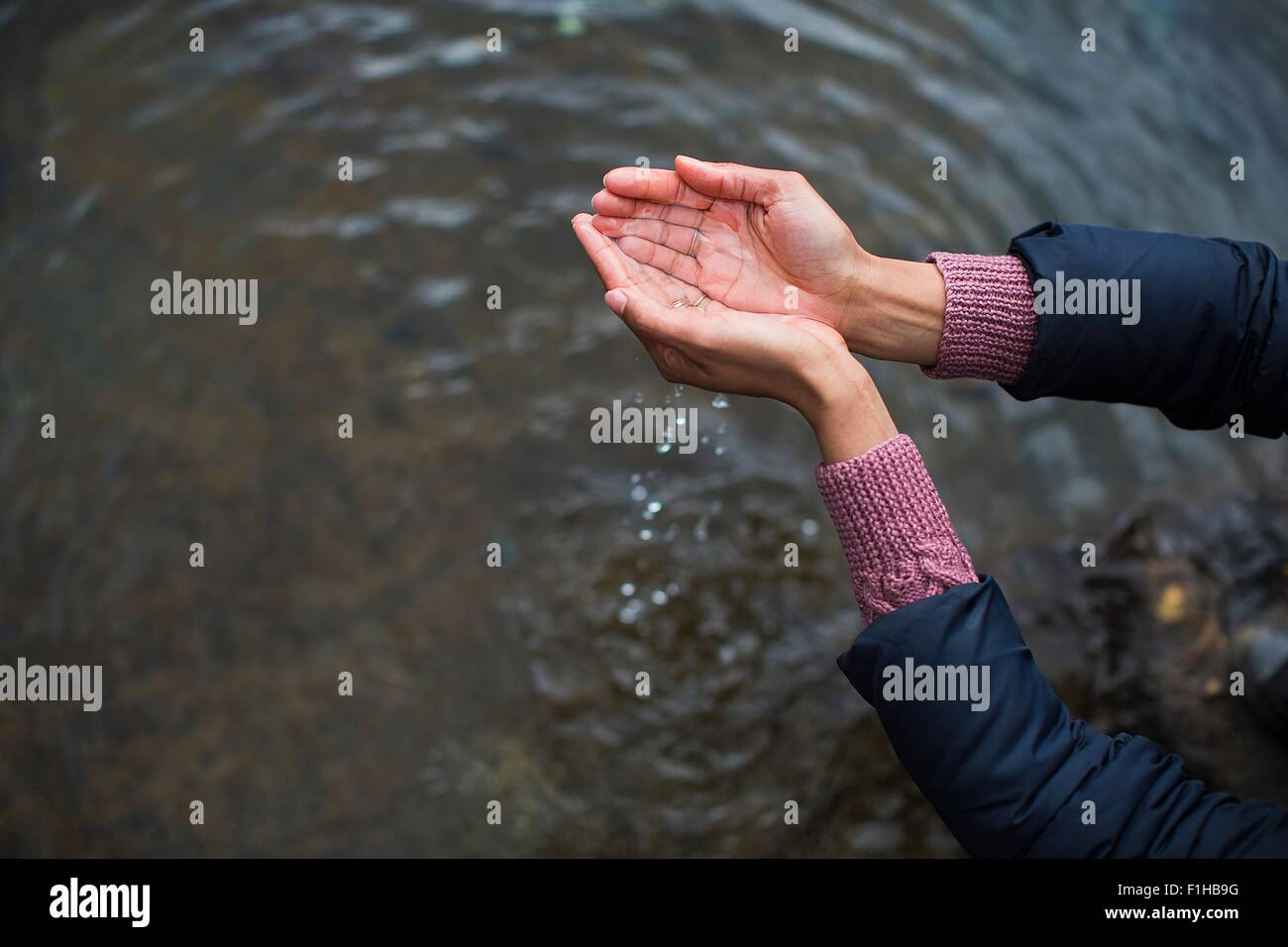 Woman holding water in cupped hands - Stock Image
