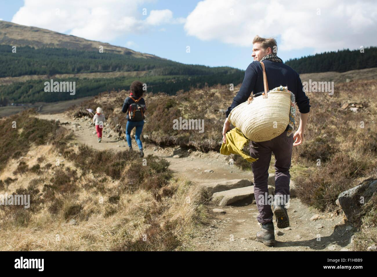 Family hiking on path in hills, Fairy Pools, Isle of Skye, Hebrides, Scotland - Stock Image